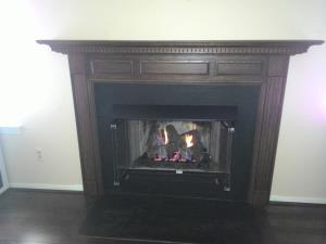 After: Zero Clearance Wood Stove Updated With Custom Mantel, Vent Free Gas Log Set, Hood And Glass Doors